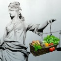 Blind lady justice holds scales on which is weighed a basket of vegetables
